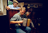 Two men playing music in the Kings Head Pub, Laxfield, Suffolk, England