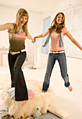 Two teenage girls (14-16) jumping around, indoor