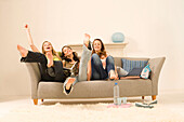 Teenage girls (14-16) sitting on sofa stretching legs high