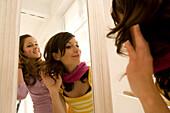 Two teenage girls (14-16) looking into mirror