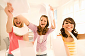 Teenage girls (14-16) throwing papers through the room