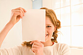 Teenage girl (14-16) holding sheet in front of face