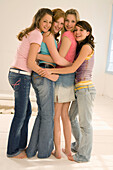 Four teenage girls (14-16) with arms around each other, smiling