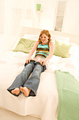 Teenage girl (14-16) sitting on bed, putting on jeans