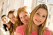 Teenage girls (14-16) sitting on window sill