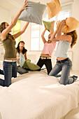 Teenage girls (14-16) having pillow fight
