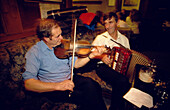 Two men playing traditional music on violin and accordion in Gus O'Connor's Pub, Doolin, County Clare, Ireland