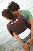 Couple in clothes embracing on the beach, portrait