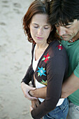 Couple embracing on the beach,eyes closed, low angle view