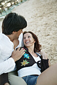 Couple in clothes embracing on beach, smiling