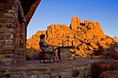 Man sitting in front of holiday bungalow, Canon Lodge, Gondwana Canon Park, Fish River Canyon, Namibia