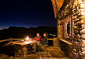 Couple sitting on porch of holiday bungalow at night, Canon Lodge, Gondwana Canon Park, Fish River Canyon, Namibia