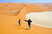 Young couple running down Big Daddy. one of the earth highest dunes, Sossusvlei. Namib desert. Namibia. Africa