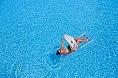 Woman reading newspaper on air mattress in pool, Apulia, Italy