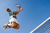 Male tennis player celebrating on court, jumping over net, Apulia, Italy