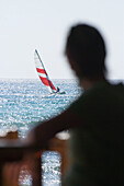 Unrecognizable person on beach, looking at sailboat on sea, Apulia, Italy