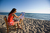 Young woman painting picture on beach, Apulia, Italy