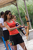 Young female archer drawing bow, Apulia, Italy