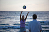 Two people playing with ball on beach, Apulia, Italy