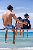 Young man and two children sitting on bench before sea shore, Apulia, Italy