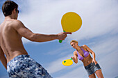 Young couple playing paddle ball on beach, Apulia, Italy