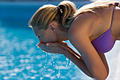 Young woman in bikini rinsing face in pool, side view, Apulia, Italy