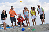 Group of people playing bocce ball on beach, Apulia, Italy