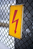 Electricity sign on a fence