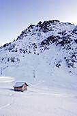 Log cabin in snowcovered landscape, Passo Pordoi, Dolomites, Italy