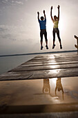 Two people jumping on jetty, arms raised