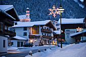 View along a street with christmas decoration in the evening, Flachau (927 m), Salzburger Land, Austria