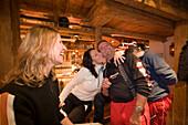 Two girls and a man dancing and enjoying an Apres-ski party at Purzelbaum Alm, Flachau, Salzburger Land, Austria
