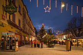 People walking over the christmas market at Hauptplatz in the evening, Schladming, Styria, Austria