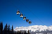 Overhead cable car and Dachstein Mountains at horizon, Hochwurzen, Schladming, Ski Amade, Styria, Austria