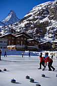 People curling on a rink, Matterhorn in background, Zermatt, Valais, Switzerland (Curling: A rink game where round stones are propelled by hand on ice towards a tee (target) in the middle of a house (circle)).