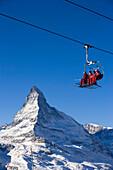 Skiers sitting on ski lift, Matterhorn in background, Zermatt, Valais, Switzerland