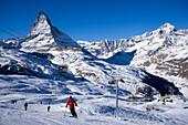 Skiers on mountain slope, Matterhorn (4478 m) in background, Zermatt, Valais, Switzerland