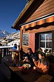 Couple sitting on terrace of Restaurant Paradies (2540 m) and eating, Findeln, Zermatt, Valais, Switzerland