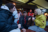 Group of young people enjoying an Apres Ski party on terrace of Papperla Pub, Zermatt, Valais, Switzerland