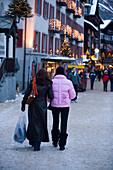 Two women walking over a shopping street, Bahnhofstrasse, Zermatt, Valais, Switzerland