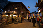 People walking over the illuminated shopping street Bahnhofstrasse in the evening, kiosk in foreground, Zermatt, Valais, Switzerland