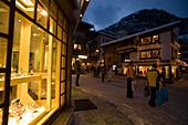 People walking over the illuminated shopping street Bahnhofstrasse in the late evening, Zermatt, Valais, Switzerland