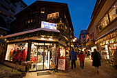 People walking over the shopping street Bahnhofstrasse in the late evening, a sports outfitters in foreground, Zermatt, Valais, Switzerland