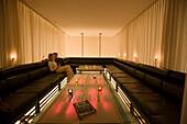 Couple sitting on lounge, tablet pc ins foreground, Vernissage Club, Design by Heinz Julen, Zermatt, Valais, Switzerland