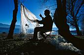 Fisherman mending his nets, Lake Chiemsee, Bavaria, Germany
