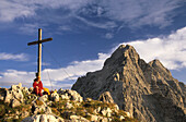 Mountaineer and summit cross with a view of the Watzmann, Berchtesgaden Range, Upper Bavaria, Bavaria, Germany