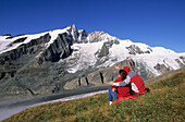 Two hikers in front of the Pasterze glacier and Grossglockner, Glockner range, Hohe Tauern national park, Carinthia, Austria