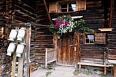 Milk cans and door with flower decorations, Pehab hut, Dachstein mountain range, Salzburg, Austria