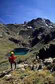 Hiker descending towards a blue, green lake Lej Languard, Upper Engadin, Grisons, Switzerland