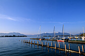 Landing stage and boats in Gstadt at lake Chiemsee with Fraueninsel, Hochgern and Kampenwand in the background, Chiemgau, Upper Bavaria, Bavaria, Germany